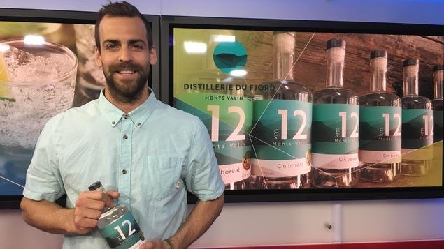 Un homme barbu tient dans ses mains une bouteille de gin KM12.