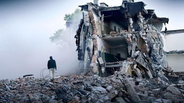 Une image du documentaire « Les Casques blancs » (« The White Helmets ») montrant un homme devant un édifice détruit par les bombes en Syrie.
