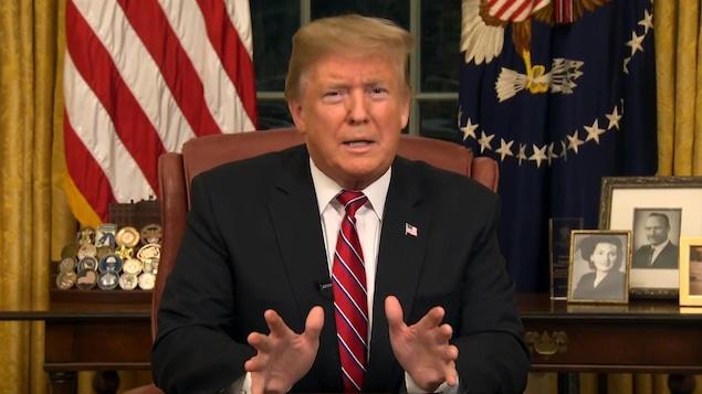 Donald Trump assis dans le bureau ovale, regardant la caméra.