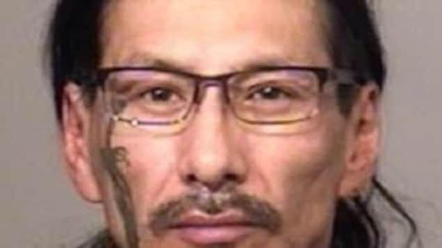 Douglas Hill portrait, il porte des lunettes, deux tatouages, un sur la joue gauche, l'autre dans le cou