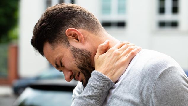 Un homme se masse le cou en raison de la douleur.