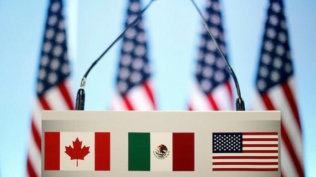 Les drapeaux du Canada, du Mexique et des États-Unis sont vus sur un lutrin avant une conférence de presse conjointe sur la clôture de la septième ronde de négociations de l'ALENA à Mexico.