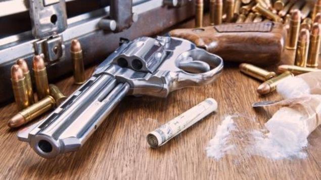 Un pistolet entouré de balles, d'un sachet de drogue et de billets de banque roulés, sur une table