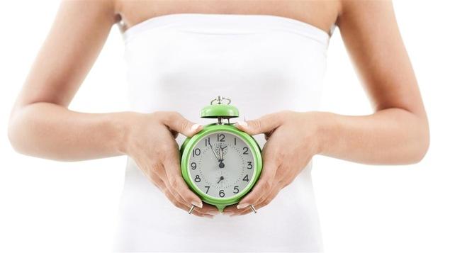 Une femme tient une horloge contre son ventre.