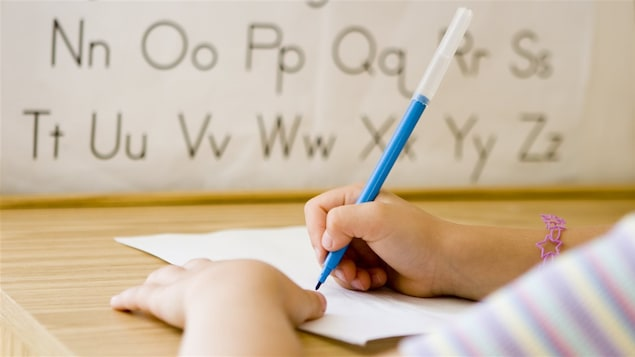 Un enfant apprend à écrire à l'école.