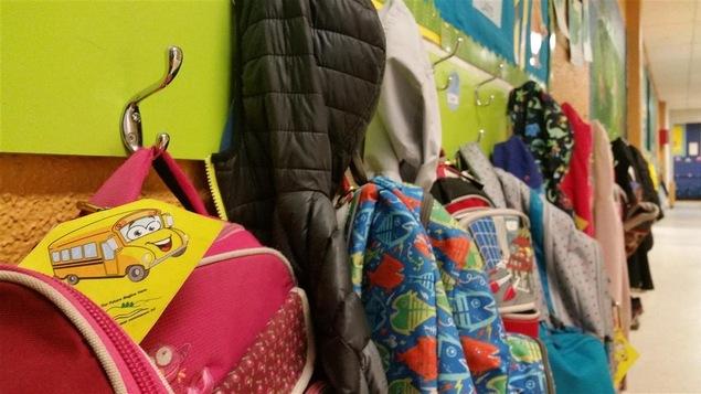 Des manteaux et des sacs à dos d'écoliers dans une école primaire