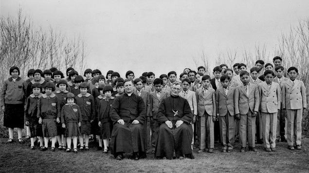 Des élèves du pensionnat autochtone Brocket, en Alberta, en 1930, sont debout en uniformes d'élèves derrière deux religieux assis.