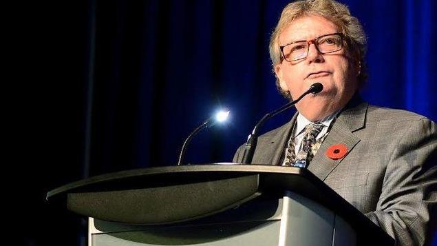 Un homme est debout derrière un pupitre équipé d'un micro lors d'un discours