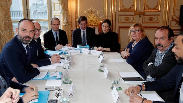 Plusieurs personnes sont assises autour d'une table.