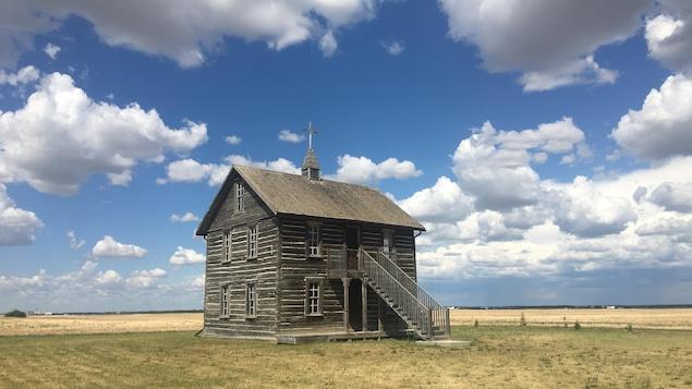 Une église en bois centenaire se dresse au milieu d'un champ, surplombé par une croix de boix.