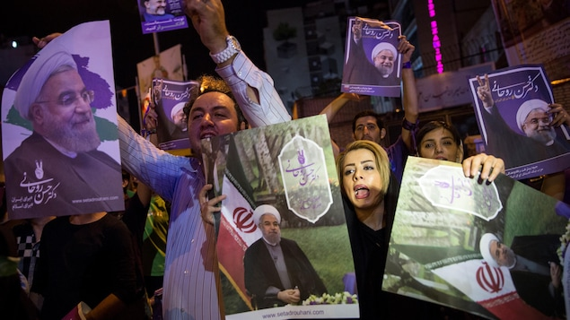 Des partisans du président sortant Hassan Rohani brandissent des affiches électorales.