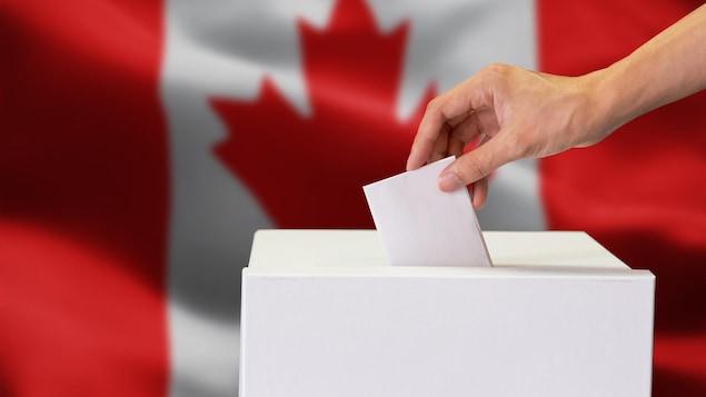 Une main dépose un bulletin de vote dans une urne.