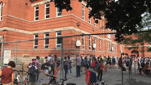 Des élèves du primaire dans une cour d'école.