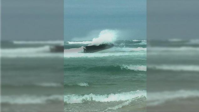 Bateau chaviré frappé par une vague