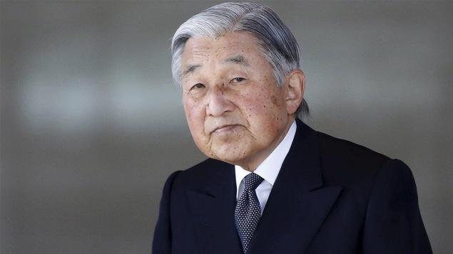 Un vieil homme asiatique aux cheveux gris et en complet, regarde la caméra.