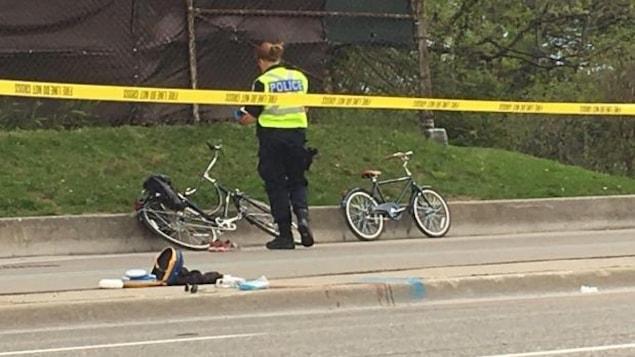 Une policière et deux vélos derrière un ruban jaune qui délimite la scène de l'accident