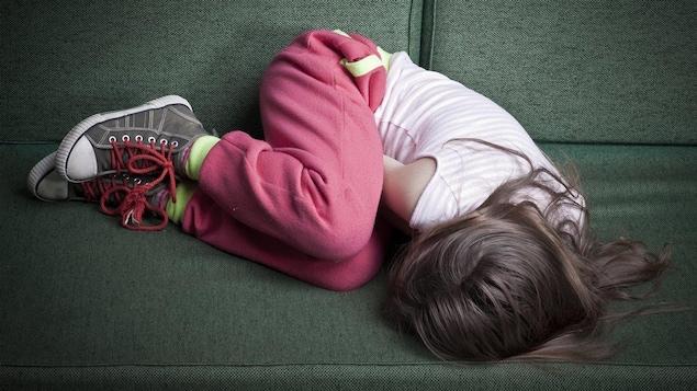 Une jeune fille est roulée en boule sur le sofa.