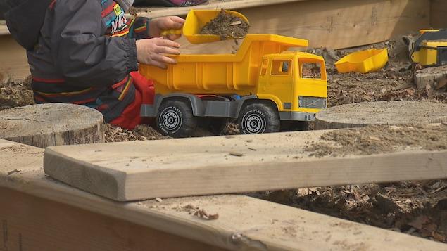 Un enfant joue avec un camion dans le sable.