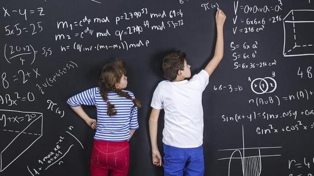 Deux enfants écrivent au tableau