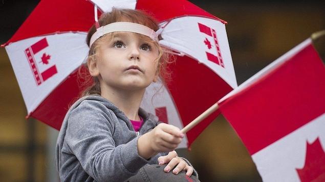Une petite fille qui tient un drapeau du Canada