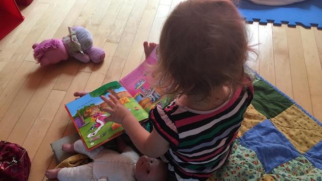 Une enfant lit un livre dans une garderie.