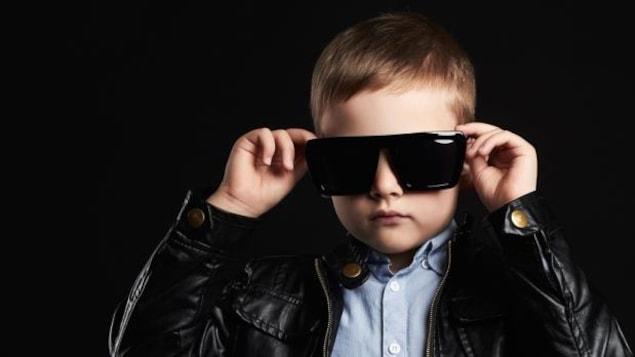 Un enfant porte des lunettes de soleil.