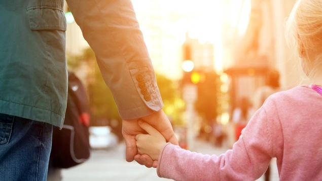 Un père et sa fille se promènent dans la rue.