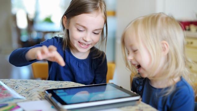 Deux fillettes rient et jouent avec une tablette