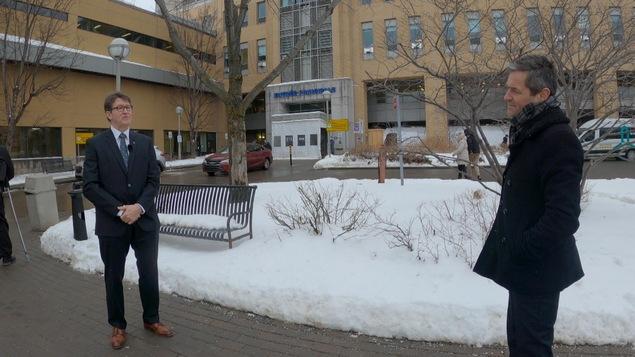 Robert Laforce et Bruno Savard en entrevue devant un hôpital, l'hiver.