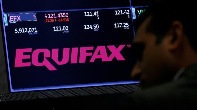 Le visage d'un homme est vu de profil, devant le logo d'Equifax qui apparaît sur un écran à la Bourse de New York.