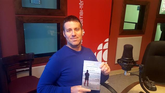 L'auteur, Éric Lépine, dans le studio de Radio-Canada en Abitibi-Témiscamingue avec son livre Simplement Différent.