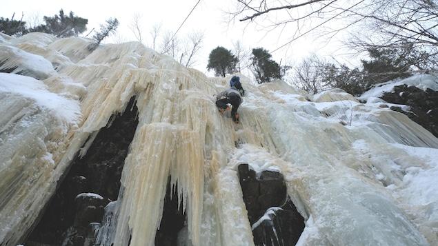 Des grimpeurs en action sur une paroi glacée.
