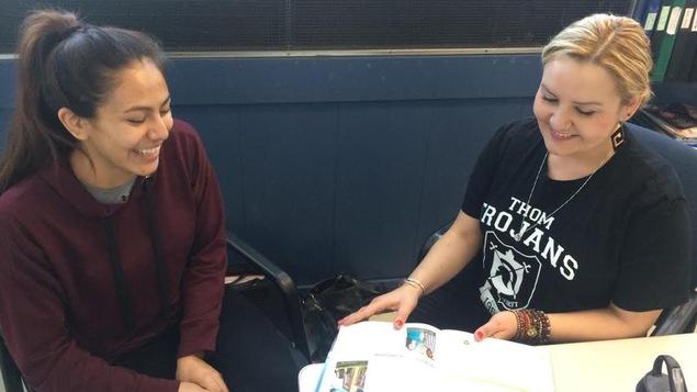Une professeure aide une étudiante autochtone.