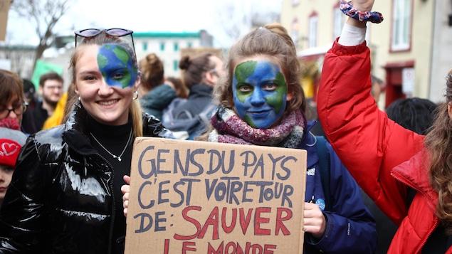 Deux adolescentes avec le visage peint en planète terre montrent leur pancarte dans une manifestation à Québec.