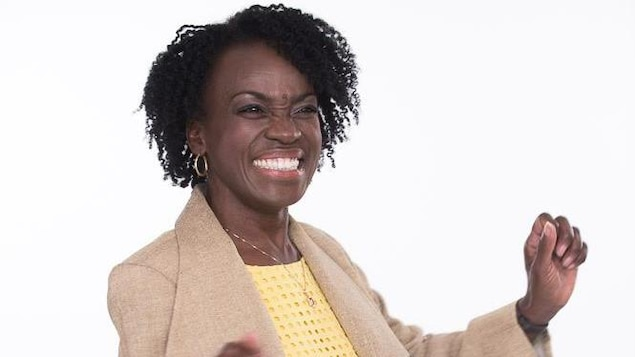 Une femme noire avec une robe jaune et une veste beige qui a les bras levés.