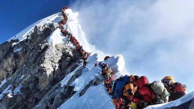 Une longue file d'alpinistes s'étire du sommet de l'Everest.