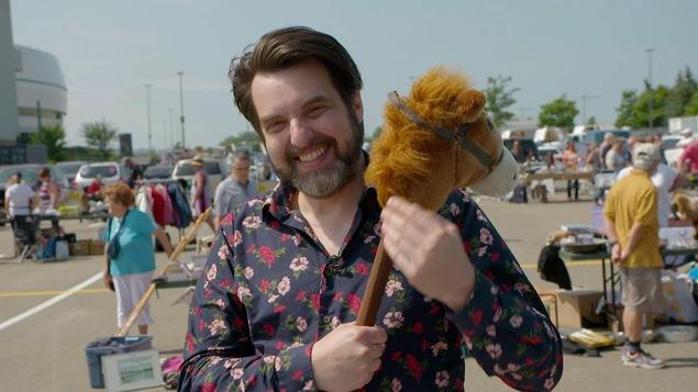 MC Gilles tient une marionnette de cheval entre ses mains.