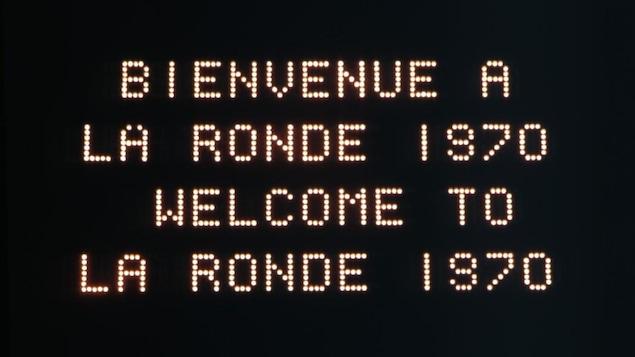 Un panneau d'affichage lumineux indique «Bienvenue à la Ronde 1970, Welcome to La Ronde 1970».