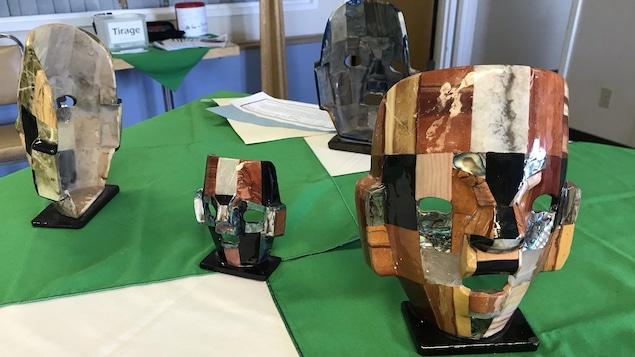 Des masques de différentes tailles représentant des visage humanoïdes constitués d'une mosaîque de carrés de différents bois, de pierres et de nacre.