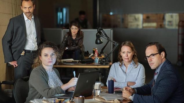 Cinq personnes sont assises dans un bureau.