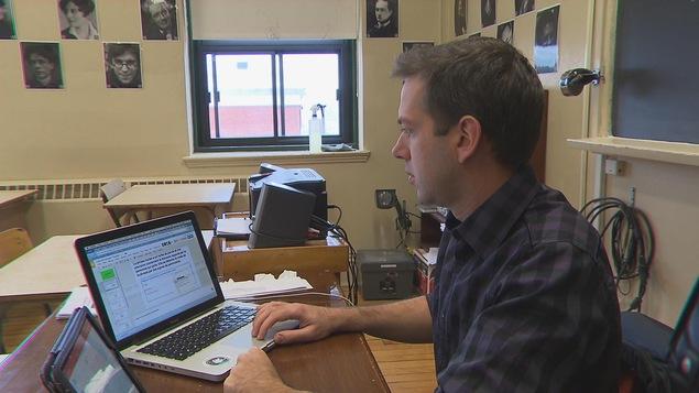 L'enseignant Félix Arguin s'affaire à répondre à des jeunes qui ont des questions concernant leur cours de français.