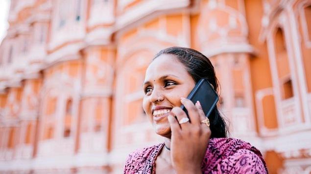 Une femme téléphone dans les rues de Jaipur, en Inde
