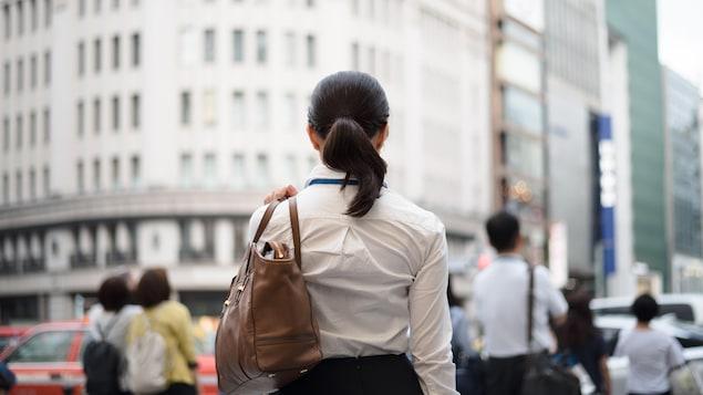 Une femme de dos se tient devant une rue achalandée d'un centre-ville.