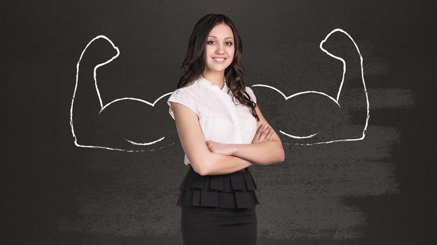 Une femme aux bras croisés devant un dessin de muscles d'homme sur un tableau.