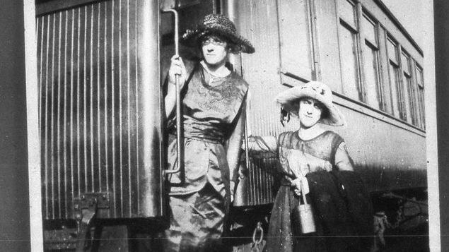 Une photo d'époque en noir et blanc. Les deux femmes portent des chapeaux d'époque et des robes longues.