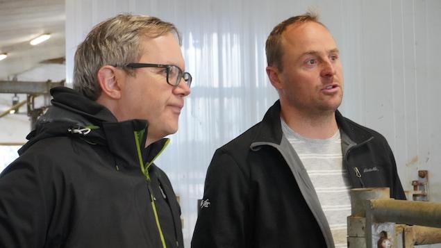 Deux hommes discutent dans une ferme.