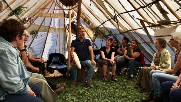 Dans une tente amérindienne, des festivaliers écoutent attentivement un conteur.