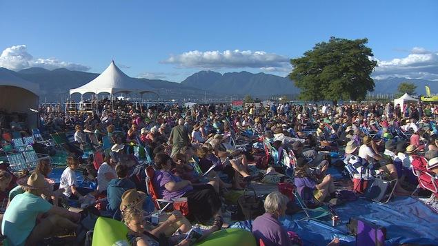 Les spectateurs de festival de folk de Vancouver assistent aux concerts avec les montagnes dans l'arrière-plan