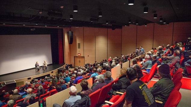 Le public est assis dans la salle de spectacle face à la scène où est assis Harold Arsenault.