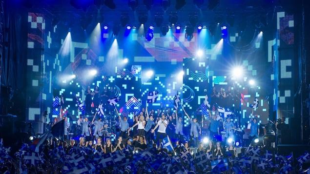 Des artistes chantent et agitent des drapeaux québécois devant le public qui lui aussi agite des drapeaux lors du grand spectacle pour célébrer la fête nationale à Montréal en 2017.